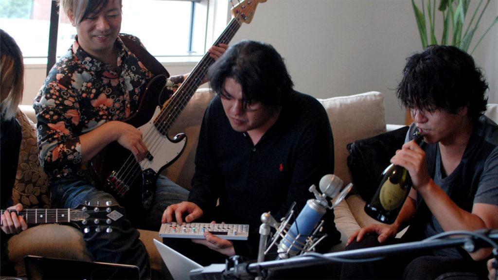 كينجي إينو يتوسط رفاقه أثناء إحدى جلسات العزف (ننصحك بالاستمتاع إلى موسيقى إينو أثناء قراءة المقال)